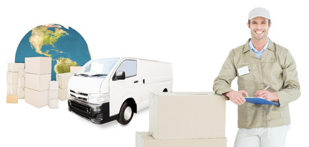 leaning on the truck: Happy delivery man writing on clipboard by cardboard boxes against logistics graphic