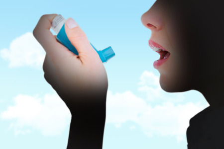 asma: Primer plano de una mujer que usa un inhalador de asma contra el cielo azul Foto de archivo