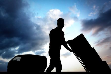 beau jeune homme: Livreur poussant chariot de bo�tes contre le ciel nuageux