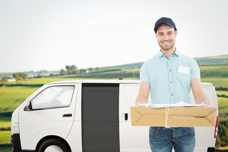 scenic landscape: Handsome courier man with parcel against scenic landscape