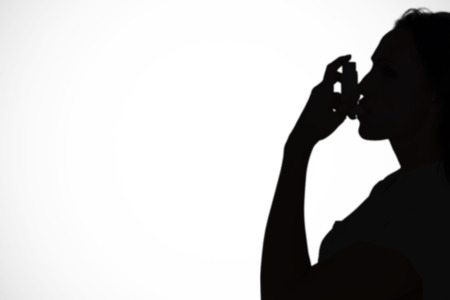 asthmatic: Asthmatic brunette using her inhaler  against white background with vignette