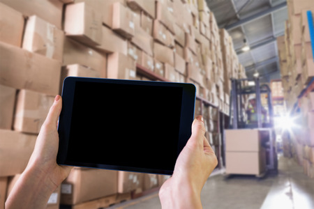 warehouse: Finger pointing to tablet against forklift machine in warehouse