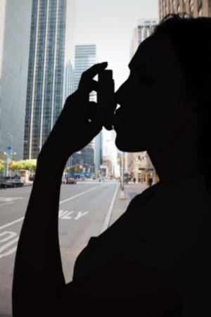 asthmatic: Asthmatic brunette using her inhaler  against new york street Stock Photo
