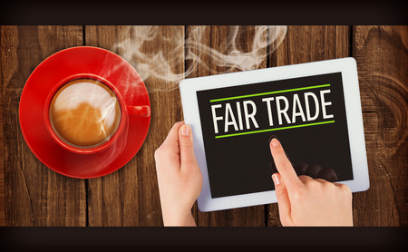 fair trade: fair trade against hand holding tablet Stock Photo