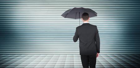 sheltering: Businessman sheltering under black umbrella against grey shutters