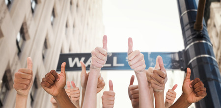 Hands showing thumbs up against wall street