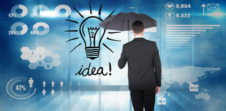 sheltering: Businessman sheltering under black umbrella against futuristic technology interface Stock Photo