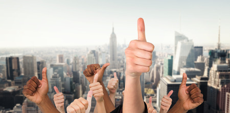 Hands showing thumbs up against new york Stock Photo