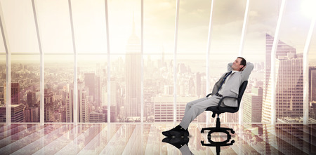 swivel chair: Businessman relaxing in swivel chair against room with large window looking on city Stock Photo