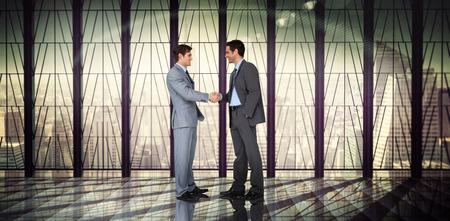 dando la mano: Empresarios agitando las manos contra la sala con gran ventanal que mira en la ciudad