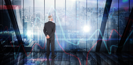 stock image: Businessman standing against stocks and shares on black background