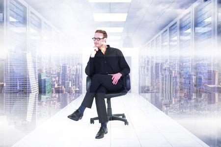 hombre pensando: Hombre de negocios pensativo sentado en una silla giratoria contra la sala de servidores con torres
