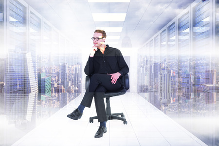 man think: Thoughtful businessman sitting on a swivel chair against server room with towers Stock Photo