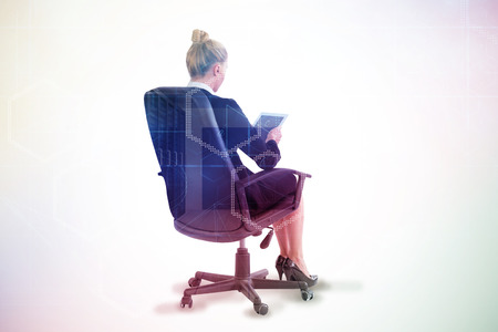 swivel chair: Businesswoman sitting on swivel chair with tablet against server room with towers Stock Photo