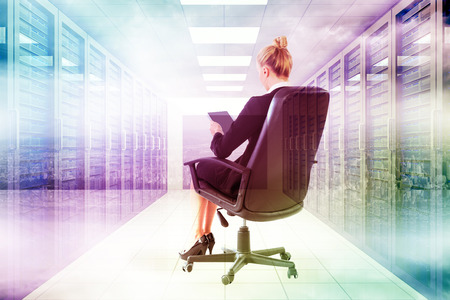 swivel: Businesswoman sitting on swivel chair with tablet against server room with towers Stock Photo