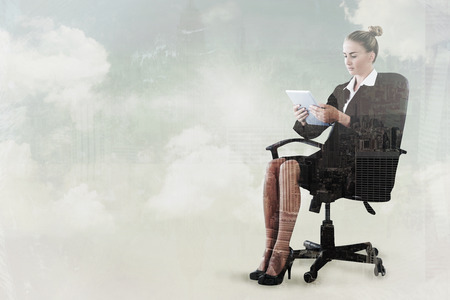 swivel chair: Businesswoman sitting on swivel chair with tablet against new york skyline Stock Photo