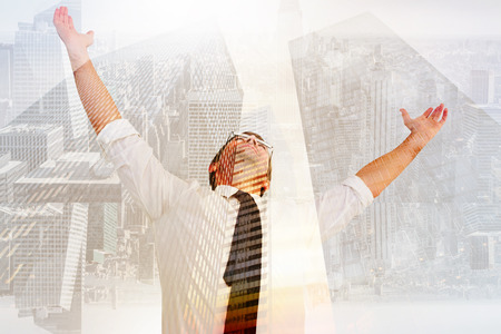 Handsome businessman cheering with arms up against low angle view of skyscrapers Reklamní fotografie