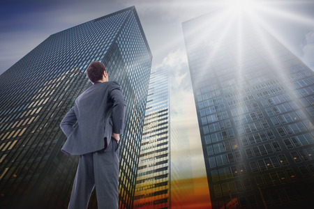 Businessman standing with hands on hips against low angle view of skyscrapers at sunset Stock Photo