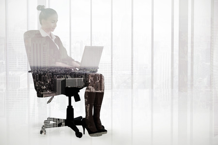swivel chair: Businesswoman sitting on swivel chair with laptop against high angle view of city skyline