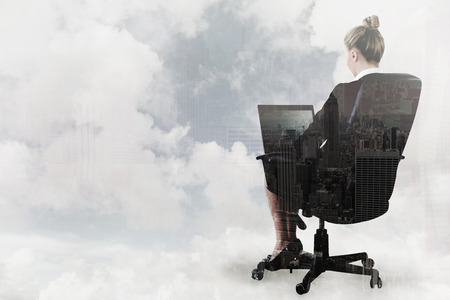 swivel: Businesswoman sitting on swivel chair with laptop against new york skyline Stock Photo