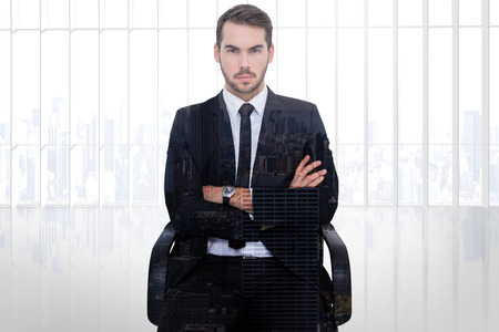 serious businessman: Serious businessman sitting with arms crossed against city skyline Stock Photo