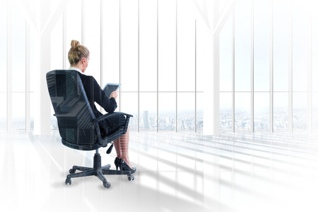 swivel chair: Businesswoman sitting on swivel chair with tablet against room with large window looking on city