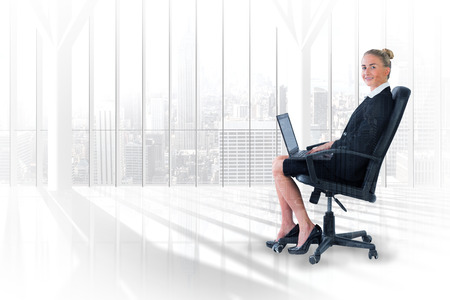 swivel: Businesswoman sitting on swivel chair with laptop against room with large window looking on city Stock Photo