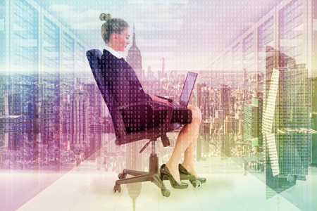 swivel chair: Businesswoman sitting on swivel chair with laptop against server room with towers
