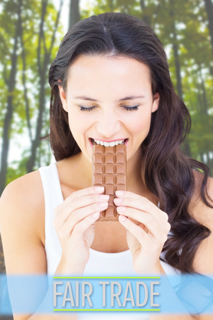 young plant: Pretty brunette eating bar of chocolate against young plant against tree trunks in forest