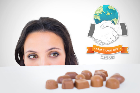 peeking: Pretty brunette peeking at chocolate against white background with vignette Stock Photo