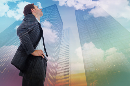 stern: Stern businessman standing with hands on hips against low angle view of skyscrapers