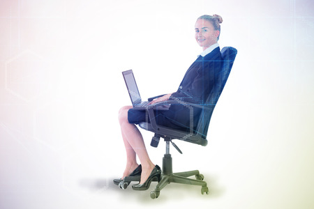 swivel chair: Businesswoman sitting on swivel chair with laptop against digitally generated server room with towers Stock Photo