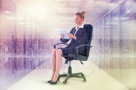 swivel: Businesswoman sitting on swivel chair with tablet against digitally generated server room with towers Stock Photo