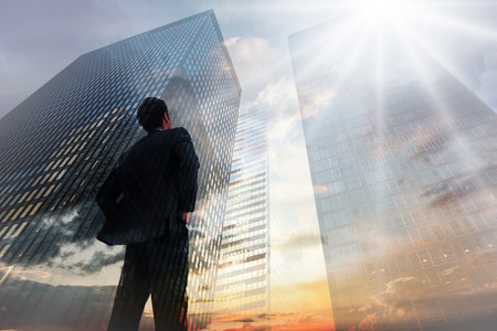 Businessman standing with hands on hips against low angle view of skyscrapers at sunset Stockfoto