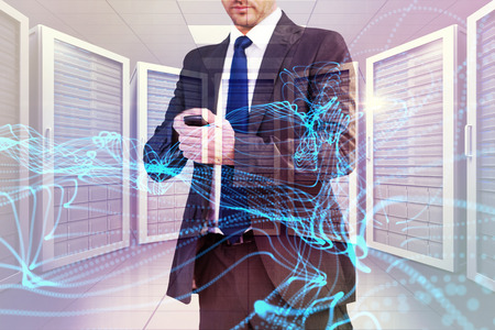 phone message: Focused businessman texting on his mobile phone against digitally generated server room with towers