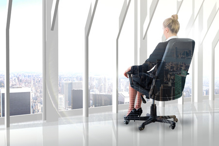 swivel chair: Businesswoman sitting on swivel chair in black suit against city skyline
