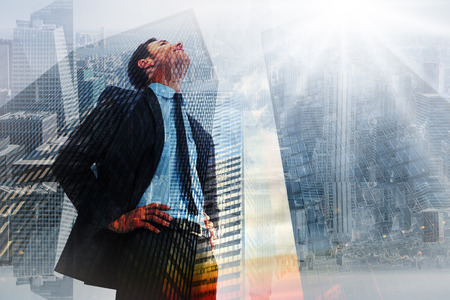 looking  up: Cheerful businessman with hands on hips against low angle view of skyscrapers at sunset Stock Photo
