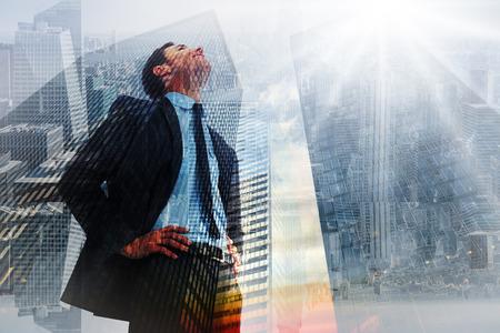 Vrolijke zakenman met de handen op de heupen tegen lage hoek mening van wolkenkrabbers bij zonsondergang