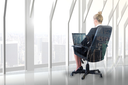swivel: Businesswoman sitting on swivel chair with laptop against city skyline