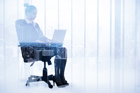 swivel: Businesswoman sitting on swivel chair with laptop against high angle view of city skyline
