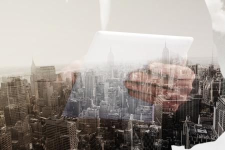 scrolling: Businessman scrolling on his digital tablet against new york skyline