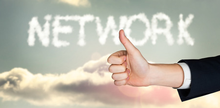 and spelling: Hand showing thumbs up against clouds spelling out network Stock Photo