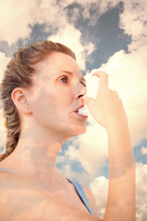 affliction: Woman using inhaler for asthma against blue sky with white clouds Stock Photo