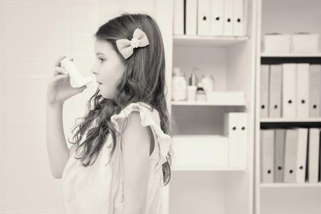 affliction: Little girl taking inhaler in medical office Stock Photo