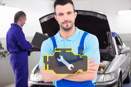 Male handyman standing arms crossed against mechanic typing on a computer next to a car Stock Photo
