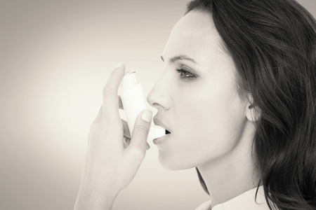 asthmatic: Asthmatic brunette using her inhaler  against grey vignette Stock Photo