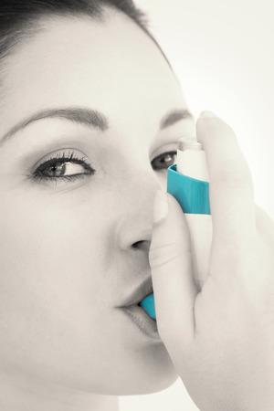 inhaler: Happy woman using astham inhaler against white background