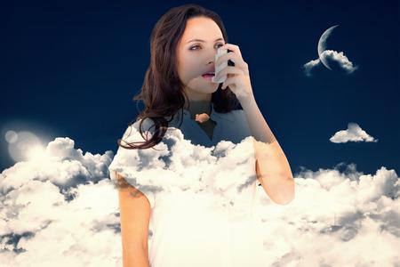 inhaler: Asthmatic brunette using her inhaler  against night sky