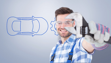 protective glasses: Handyman wearing protective glasses while holding wrench against grey vignette Stock Photo