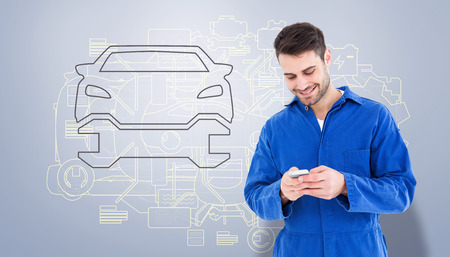 text messaging: Male mechanic text messaging through mobile phone against grey vignette